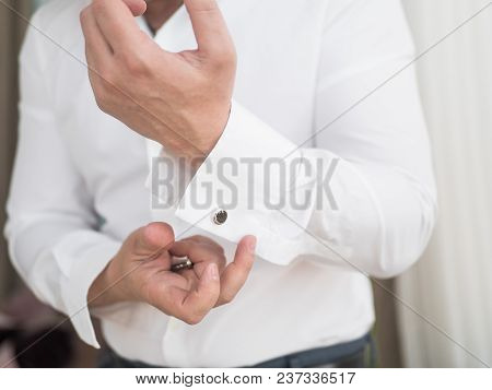 Groom Is Holding Hands On The Tie, Wedding Suit. Close Up Of A Hand Man How Wears White Shirt And Cu