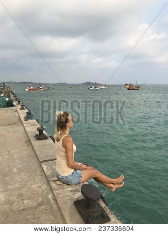 Rear View Of A Girl Sitting On A Pier.