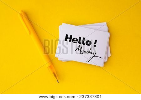 The Yellow Pen And Stacking Of  White Business Card With Hello Monday Message On Vibrant Yellow Back