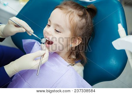 Child Lies With Open Mouth And Napkin On Chest In Comfortable Dentist Chair And Doctor In Sterile Ru