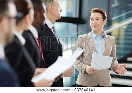 Confident female business leader with papers making report about the latest upgrades of financial rates for her business team at briefing
