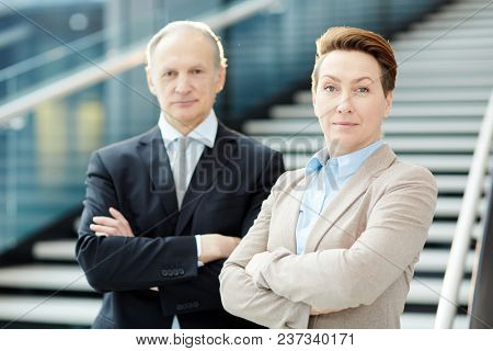 Elegant mature businessman and businesswoman looking at camera with crossed arms by staircase of airport lounge