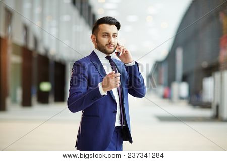 Young confident broker in formalwear talking to one of his clients on smartphone during travel