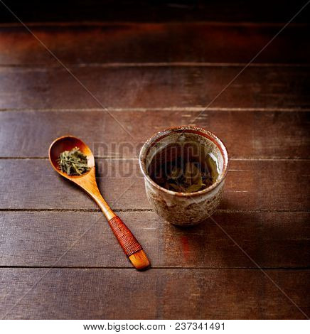 Green tea (sencha) in a traditional, japanese tea cup and sencha leaves on a wooden  tea spoon. Dark wooden background.