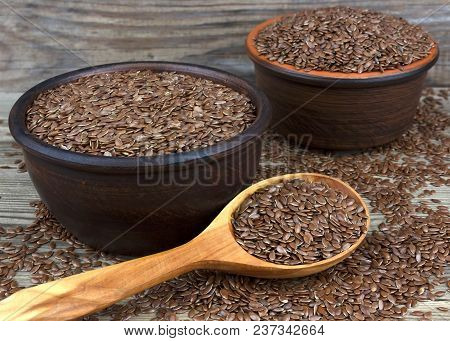 Flax Seeds In Bowl With Scattered Grains On Wooden Background With Wooden Spoon. Also Known As Linse