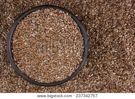 Flax Seeds In Bowl With Scattered Grains On Wooden Background. Also Known As Linseed, Flaxseed And C
