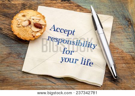 Accept responsibility for your life - inspirational handwriting on a napkin with an almond cookie