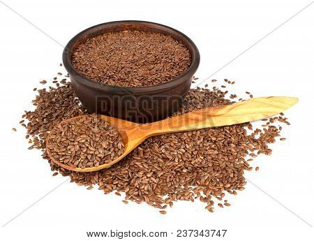 Flax Seeds In Ceramic Bowl With Wooden Spoon Isolated On White Background. Also Known As Linseed, Fl