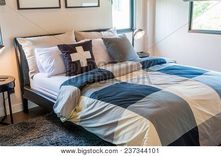 Black And White Pillows Learnind Against Headboard And Classic Lamp On Table With Frames On White Wa
