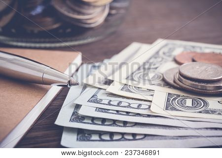 Money Banknote Us Dollar And Coins Put On Wooden Table With Silver Pen, Notebook And Saving Jar On B