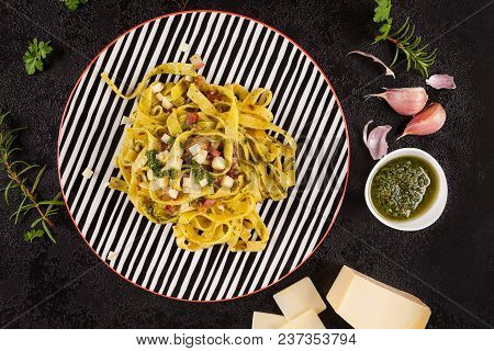 Spaghetti Aglio E Olio On Plate With Ingredients Garlic, Herbs, Parmesan Cheese From Above On Black