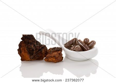 Inonotus Obliquus, Chaga Pieces And Gel Capsules On Spoon Isolated On White Background. Medicinal Mu