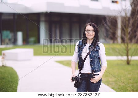 A Professional Photographer Performs His Work. Attractive Young Woman Talking Pictures Outdoors