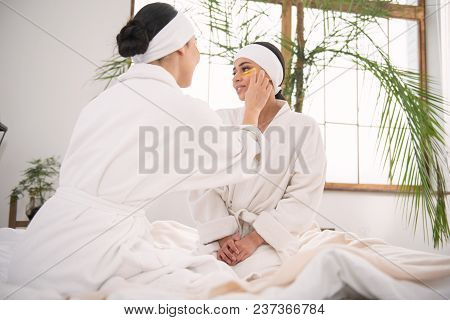 Visit To The Spa. Pleasant Young Woman Helping Her Girlfriend To Put An Eye Patch While Visiting The