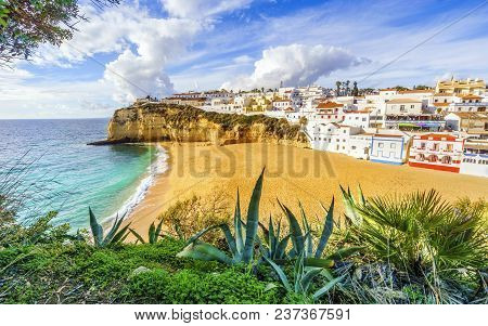Sandy Beach Next To Cliffs And White Architecture In Carvoeiro, Algarve, Portugal