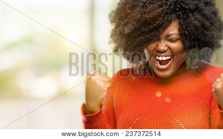 Beautiful african woman happy and excited celebrating victory expressing big success, power, energy and positive emotions. Celebrates new job joyful, outdoor