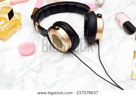 Golden Headphones And Cosmetics On A Marble Background. Feminine Desk