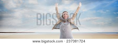 Woman in coat and scarf celebrating on beach with plane in sky