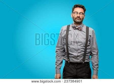 Middle age man, with beard and bow tie making funny face fooling
