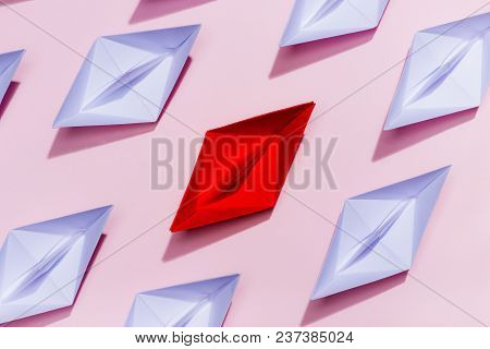 Leadership Concept. Red Paper Ship Leading Among White