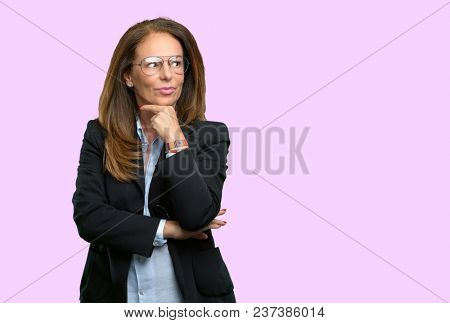Middle age business woman thinking thoughtful with smart face, expressing question and doubt. Imagine the solution