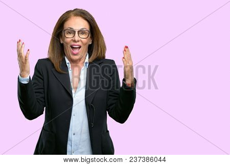 Middle age business woman happy and surprised cheering expressing wow gesture