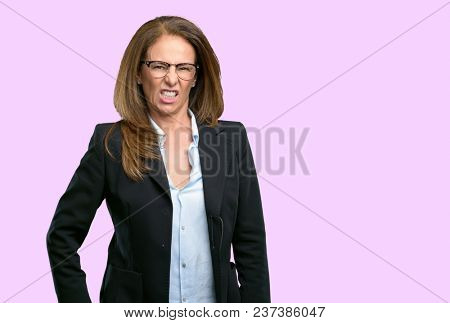 Middle age business woman angry and stressful frowns face in dissatisfaction, irritated and annoyed, expressing anger