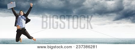 Business man with laptop celebrating against grey clouds and water