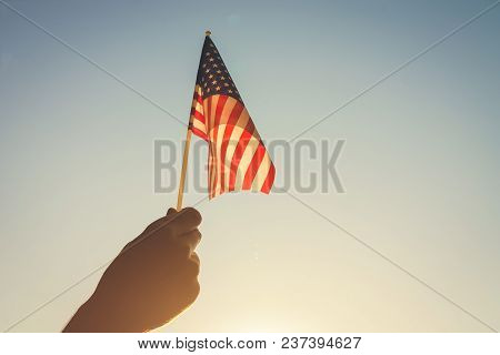 Man Holding Usa Flag Against The Blue Sky. Celebrating Independence Day Of America