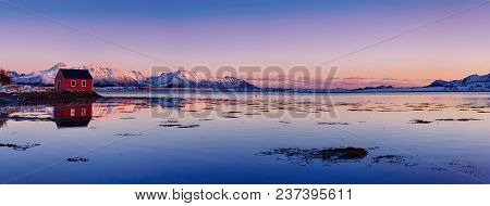 Landscape With Beautiful Winter Lake, Red Rorbu House And Snowy Mountains At Sunset At Lofoten Islan