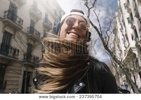 Woman With Headphones On The Street