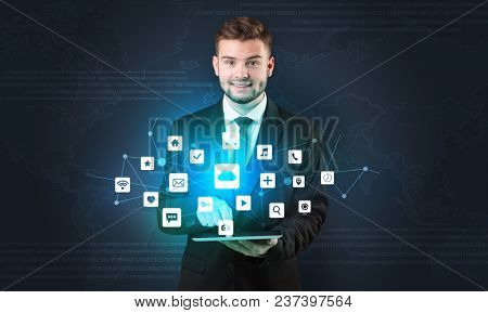 Handsome businessman in suit with tablet on his hand and application icons above