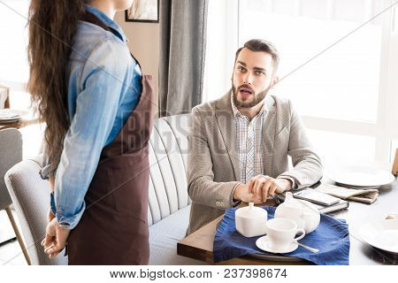 Pensive Handsome Businessman In Light Gray Jacket Sitting At Table With Teapot And Cup And Asking Wa