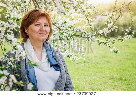 Happy Middle-aged Woman Walking In Spring Garden. Mother's Day Concept