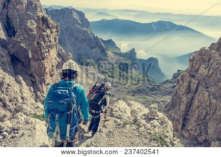 Pair Of Mountaineers Walking A Mountain Path. Spectacular Views Are Surrounding Them.