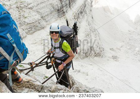Happy Climber Reaching The Summit Of Ladder. Climbing Via Ferrata In Brenta Dolomites.