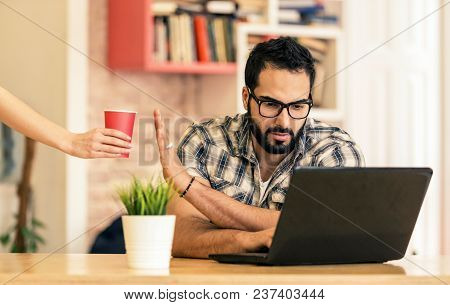 Concentrated Freelance Worker, Bearded Handsome Man Working With Laptop And Refusing Cup Of Coffee F