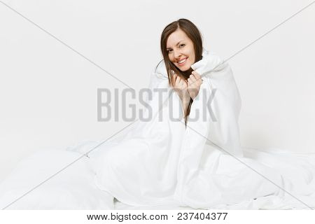 Young Brunette Woman Sitting In Bed With White Sheet, Pillow, Wrapping In Blanket On White Backgroun