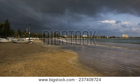Seashore Landscape. Fishing Boats In Sri Lanka During Sea Storm Under Heavy Clouds As Seen From The
