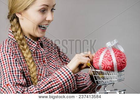 Happy Woman Holding Shopping Cart With Brain Inside. Clever, Responsible Buying Concept.