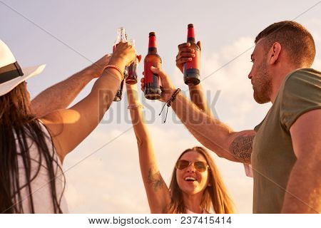 Cheerful Hilarious Young Friends Raising Hands With Beer Bottles And Cheering For Perfect Vacation W