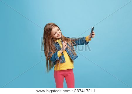 Happy Teen Girl Standing, Smiling Isolated On Trendy Blue Studio Background. Half-length Portrait. Y