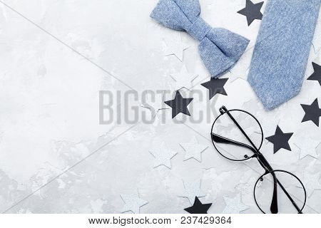 Happy Fathers Day Background With Eyeglasses, Necktie And Bowtie On Stone Table Top View In Flat Lay