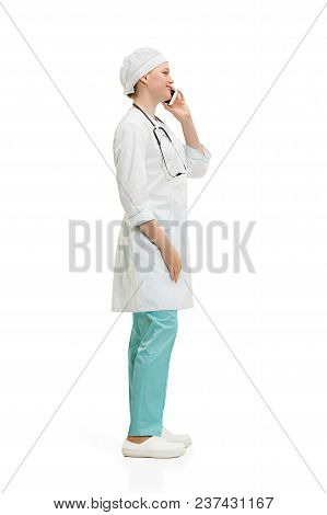 Profile Of Beautiful Young Woman In White Coat Posing At Studio With Mobile Phone. Full Length Shot