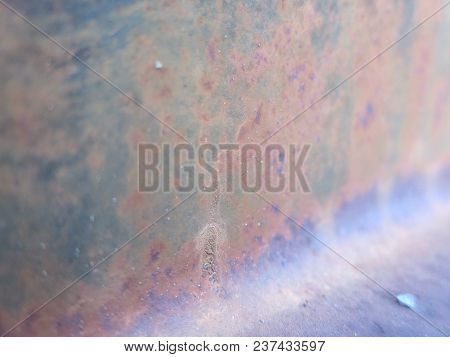 A Rusty Bbq Grill Lid Bears The Appearance Of An Outer Space Nebula.
