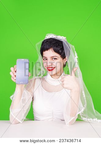 Caucasian Fiancee Holding A Mobile Phone And Pointing At It. Young Fiancee With A Mobile Phone. Fian