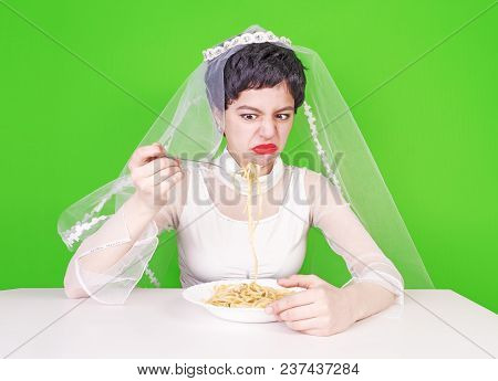 Pasta. Macaroni. The Bride Eats With Disgust And Smarts Into The Camera On A Green Background