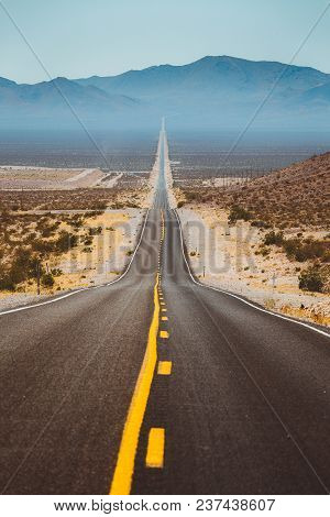 Classic Vertical View Of An Endless Straight Road Running Through The Barren Scenery Of Famous Death
