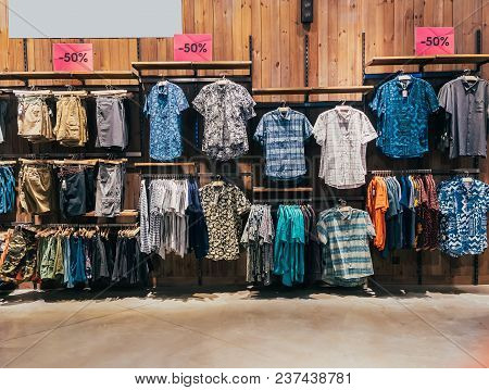 Boys Department In Clothing Store. Shop Of Men's Clothing. Showcase Rack With Shirts. Shelves With C