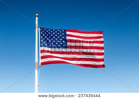 Classic View Of Usa Flag Waving In The Wind Against Blue Sky On A Beautiful Sunny Day In Summer, Uni